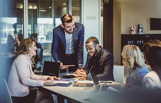 Fem menn og kvinner i kontorlandskap. Foto.